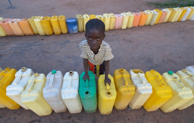 A boy guards a row of water jugs in the Rhino Refugee Camp in Uganda. Water can only be obtained during the day because pumps are solar-powered. Uganda is housing 1 million refugees from South Sudan. (CNS/Paul Jeffrey)