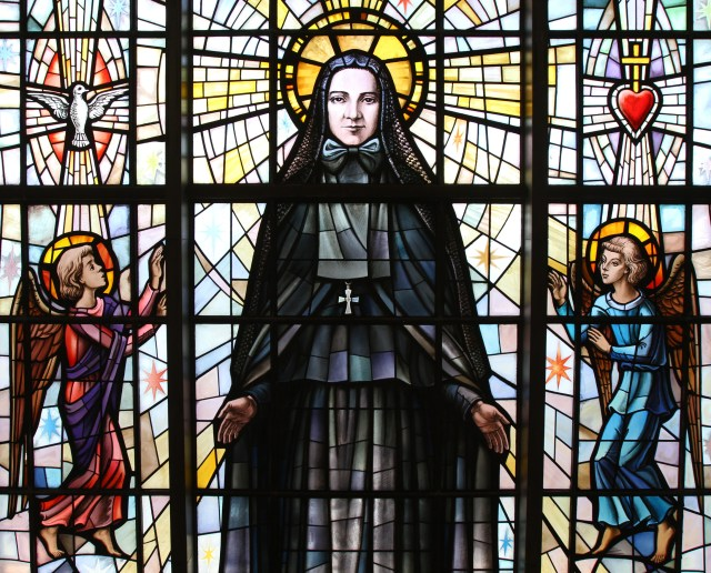 St. Frances Xavier Cabrini is depicted in a stained-glass window at the saint's shrine chapel in the Washington Heights section of New York City. Her remains rest in a glass casket under the altar in the shrine.(CNS file/Gregory A. Shemitz)
