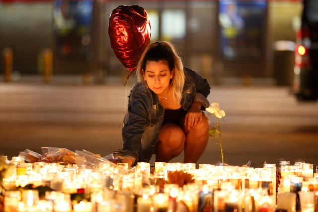 A woman lights candles at a makeshift vigil on the Las Vegas Strip Oct. 2 following a mass shooting at an outdoor country music festival. (CNS/Reuters)