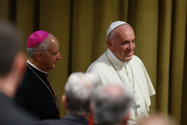 Pope Francis arrives to address participants at an encounter marking the 25th anniversary of the Catechism of the Catholic Church at the Vatican Oct. 11. Also pictured is Archbishop Rino Fisichella, president of Pontifical Council for Promoting New Evangelization. (CNS/Paul Haring)