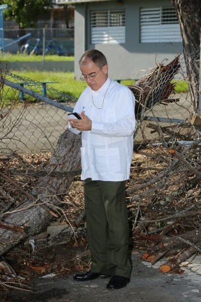Archbishop Roberto Gonzalez Nieves of San Juan, Puerto Rico, talks on his cellphone amid debris Oct. 25, more than one month after Hurricane Maria devastated the island. The archbishop's residence was operating on a generator that could only be on for a portion of the day, so he had to use his cellphone outside at other times. (CNS/Bob Roller)