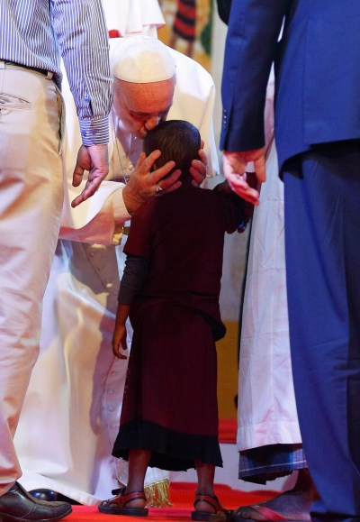Pope Francis kisses a child as he meets Rohingya refugees from Myanmar during an interreligious and ecumenical meeting for peace in the garden of the archbishop's residence in Dhaka, Bangladesh, Dec. 1. (CNS/Paul Haring)