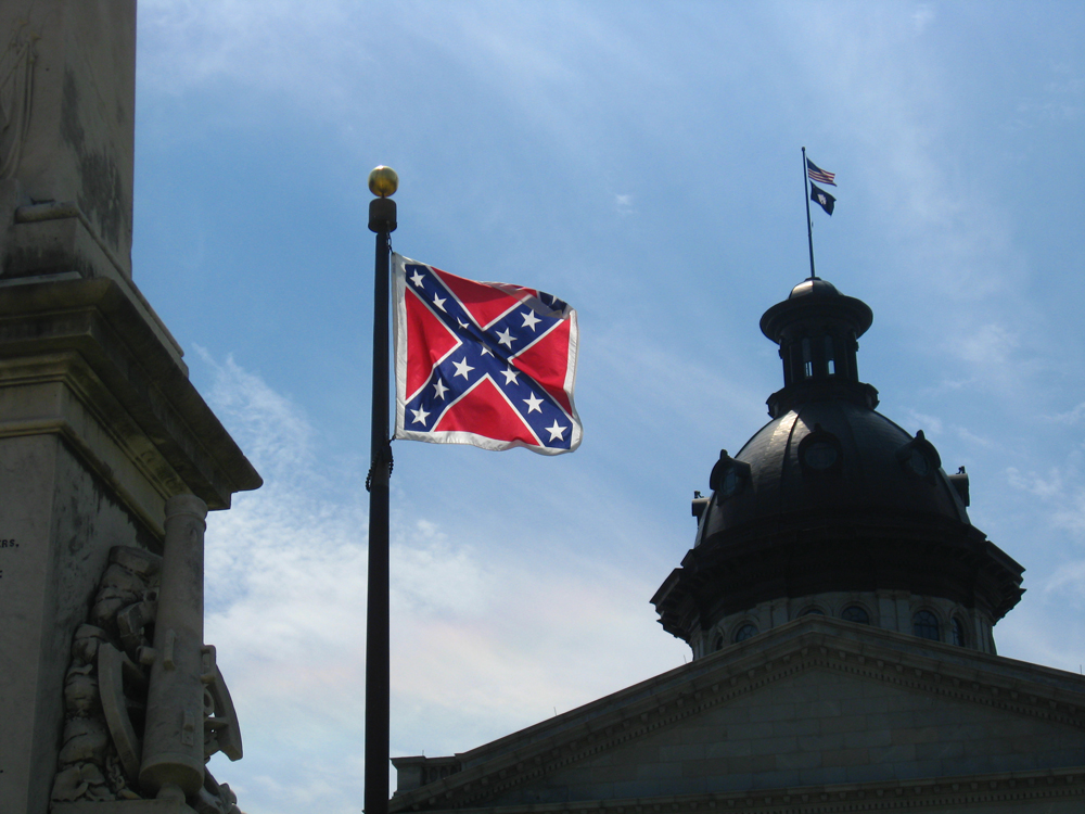 The Confederate flag flying next to the dome of a building.