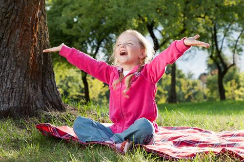 5-jähriges Mädchen sitzt auf Picknickdecke und breitet fröhlich ihre Hände aus