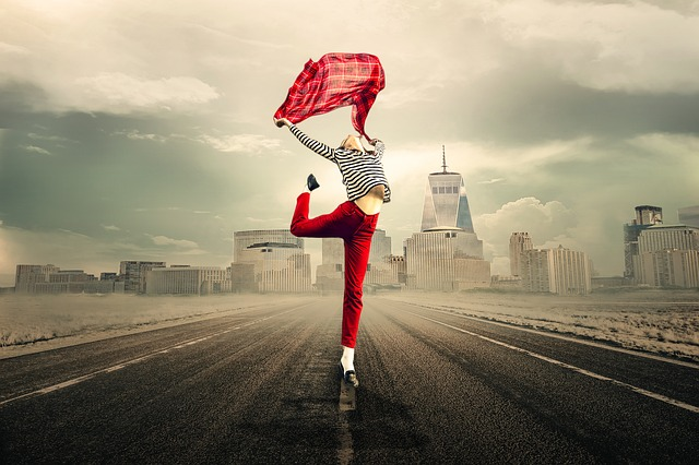 Emotionale Wunden und Traumaspuren heilen mit Tiefer Empathie: Frau tanzt mit Tuch vor Landschaft, fröhlich, lebenslustig, energetisch