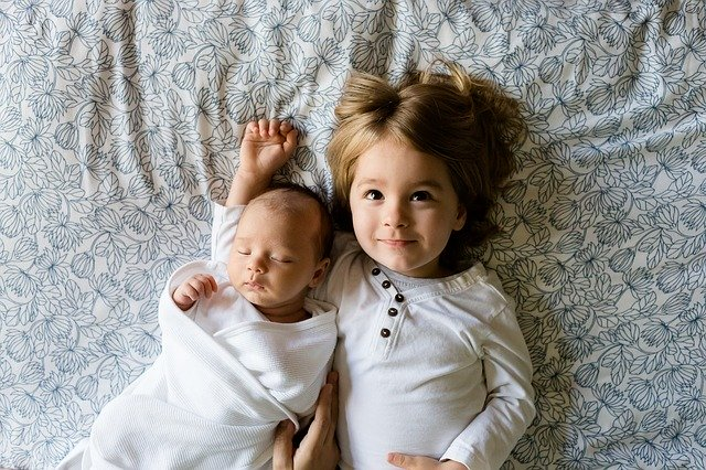 zwei Kinder liegen Arm in Arm, Baby und 4 Jahre