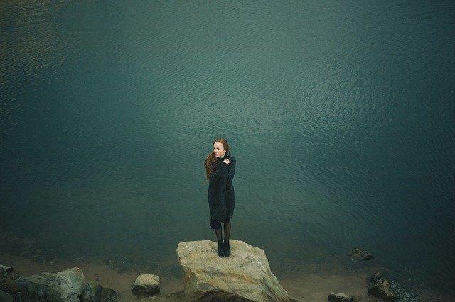 Frau im Mantel steht auf Stein am See, sie wirkt verloren und traurig