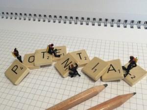 Minitaucher auf Scrabble-Buchstaben suchen nach POTENTIAL