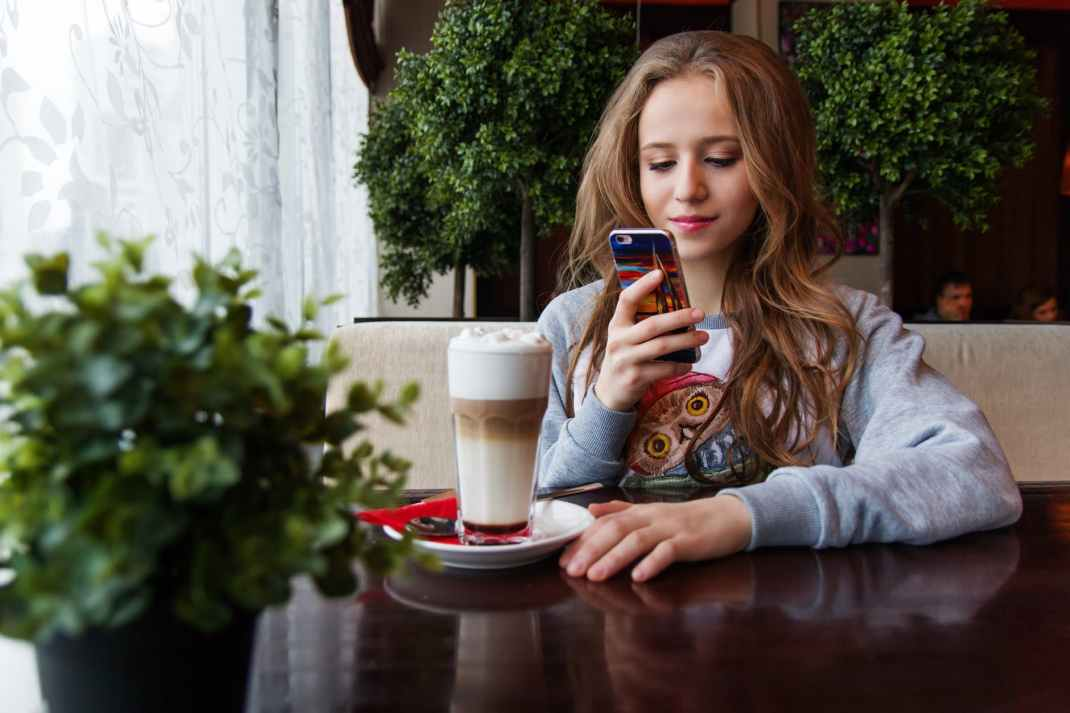 portrait of woman photographing with smart phone