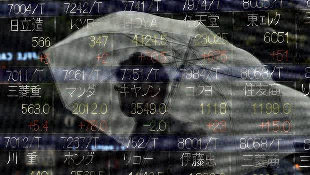 A pedestrian is reflected on a share prices board in Tokyo on August 26, 2015. Tokyo shares rebounded at the morning session, from six days of losses after China cut interest rates in a bid to shore up confidence in the world's number two economy and end a stock market slump. (YOSHIKAZU TSUNO/AFP/Getty Images)