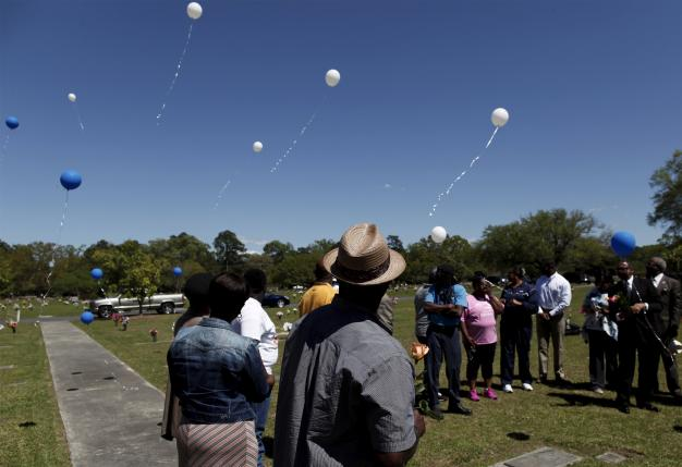 Rodney Scott (C), brother of the late Walter Scott, watches as balloons are released as relatives and friends gathered to remember Scott, at Live Oak Memorial Gardens in Charleston, South Carolina, April 4, 2016. REUTERS/Randal Hill
