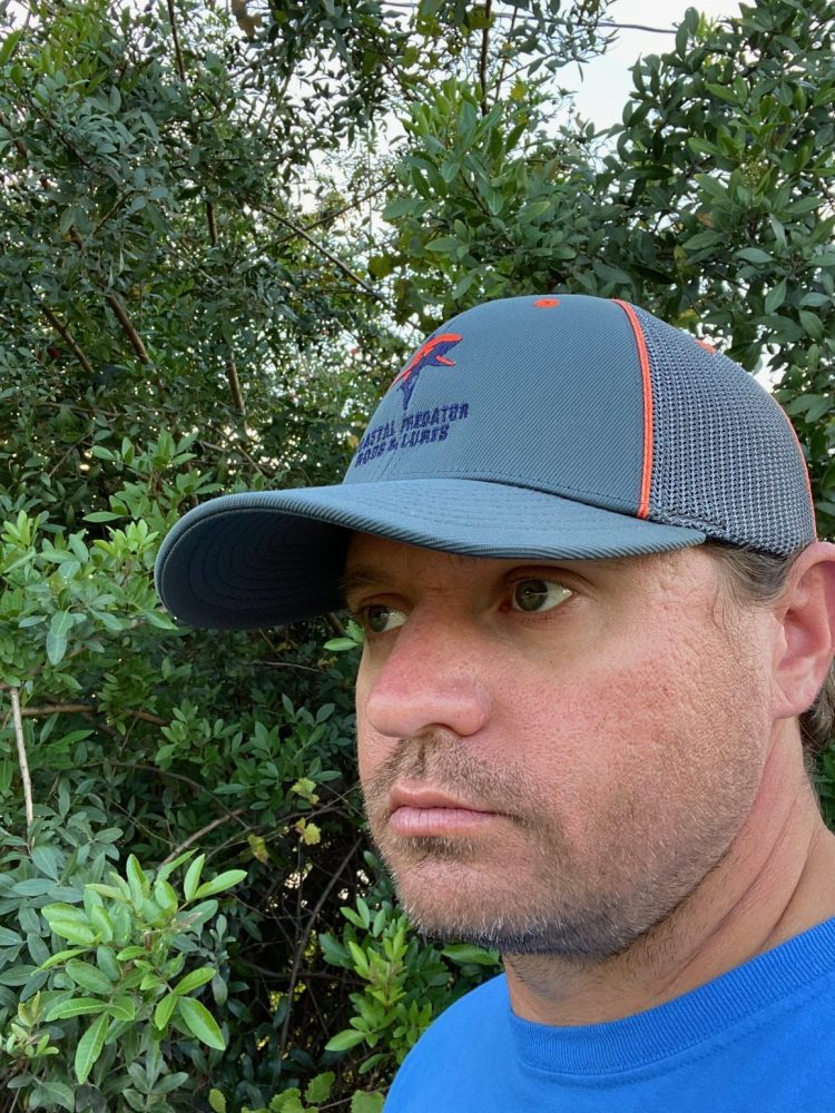 Grey Flexfit hat with Coastal Predator Rods and Lures. Hat has Orange piping and orange and blue business logo.