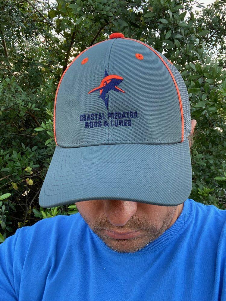 Coastal Predator Flexfit hat. Grey hat, orange piping. Orange and blue shark with blue coastal predator logo.