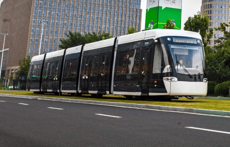 Electric low-floor tram on a grassy rail line in the city.