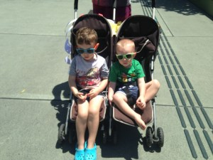 The 2 boys (toddler and threenager) in their double pushchair looking cool in their sunnies on the streets of Brisbane