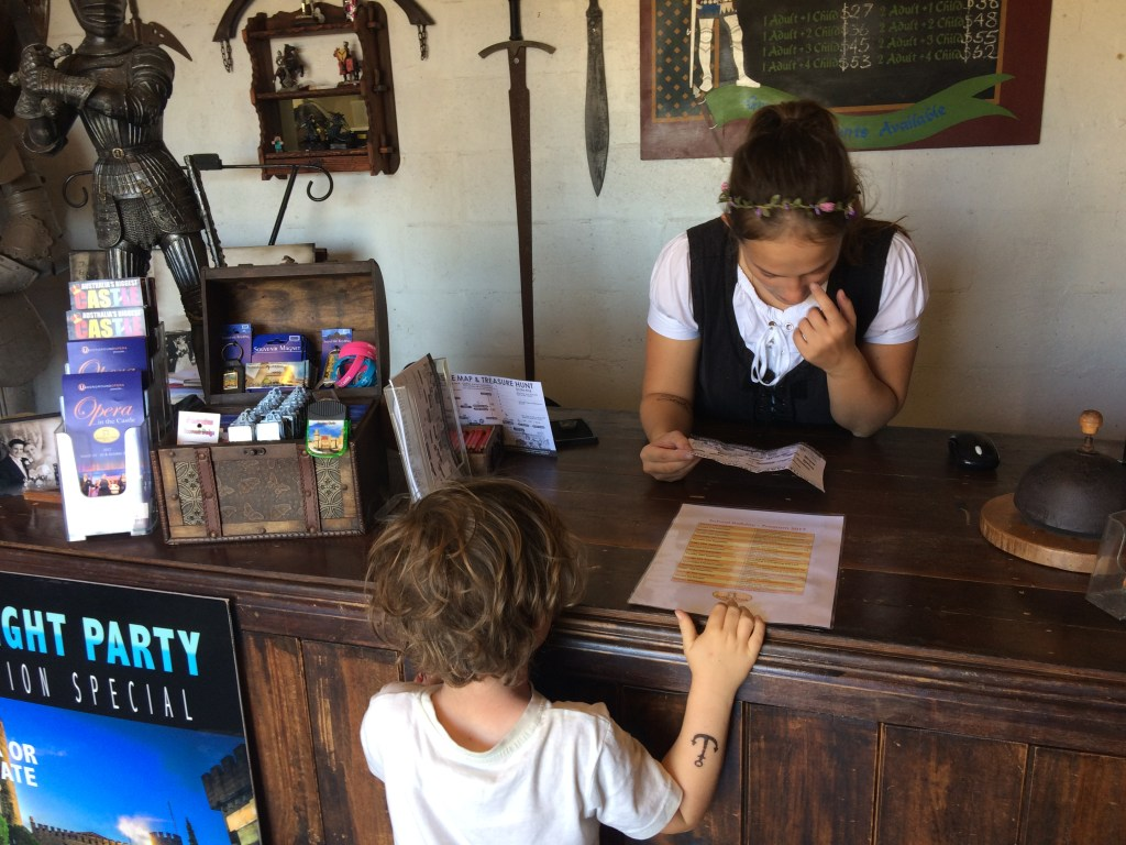 A girl dressed in medieval costume serving a young boy at Sunshine Castle