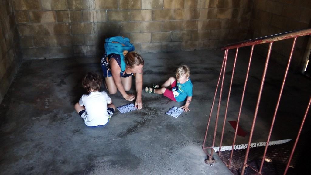 Mum and boys sitting on castle floor doing treasure hunt
