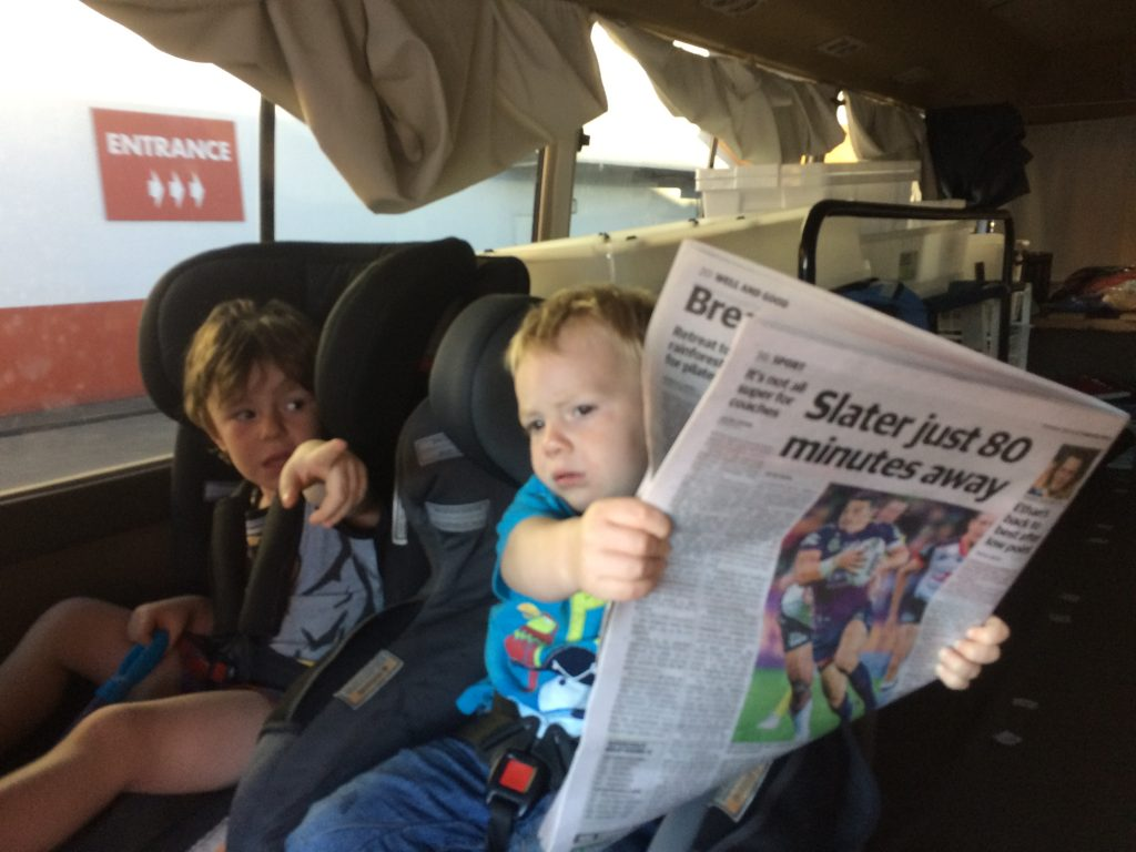 Young kids reading a newspaper