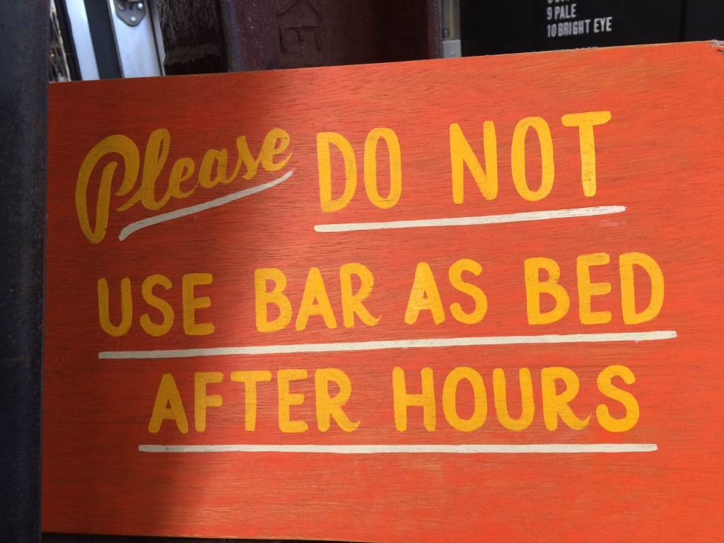A sign reading 'please do not use bar as bed after hours'