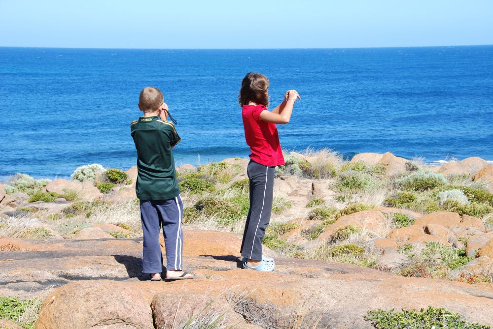 Two children looking out over the wide ocean taking holiday photos
