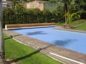 Cubierta de piscina enrollable dentro un banco de madera