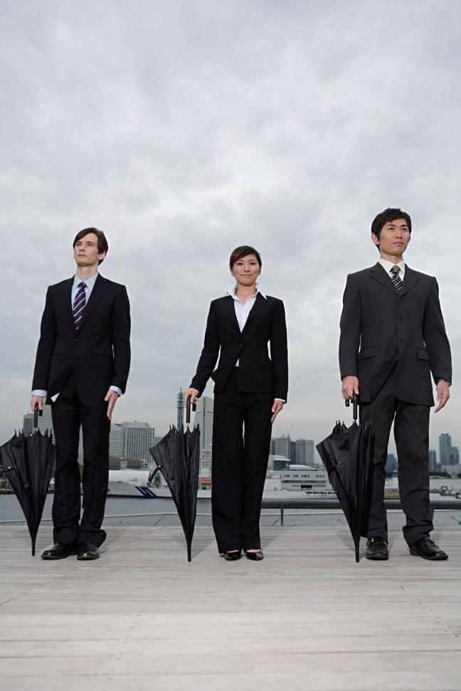 Businesspeople holding umbrellas