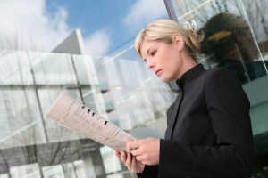 A beautiful blonde business woman reading newspaper
