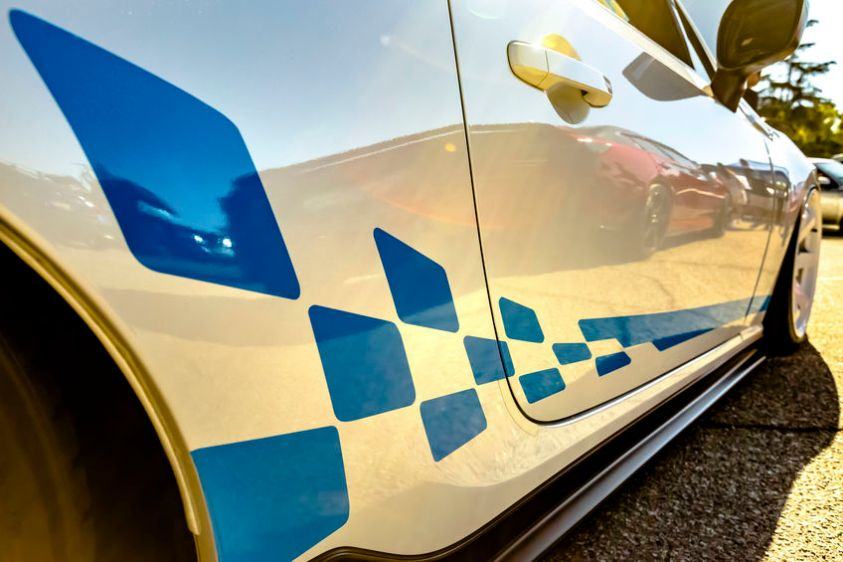 Racing decals on white car with golden reflection on the car handle