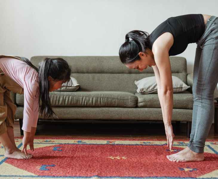 happy barefoot asian woman and adorable daughter stretching body together at home