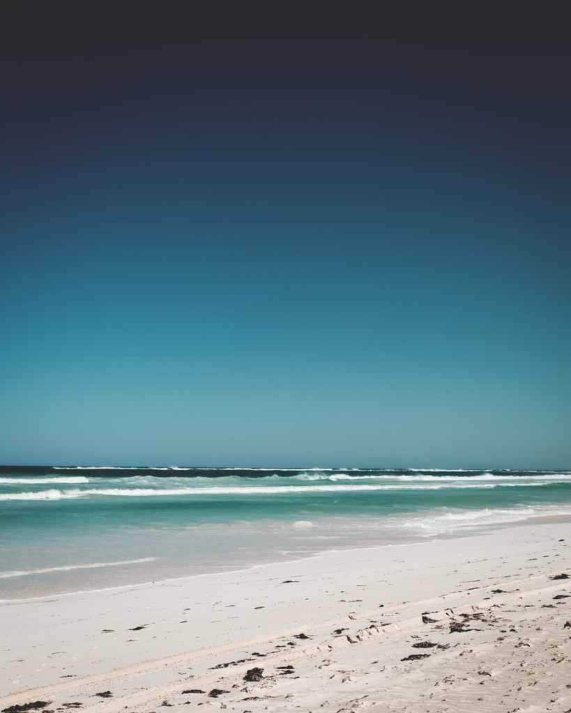 sandy coast of wavy powerful ocean under cloudless blue sky