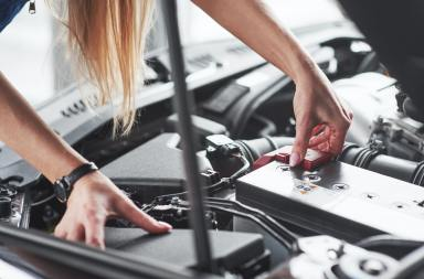 Remowing old battery. Car addicted woman repairs black car indoors in garage at daytime