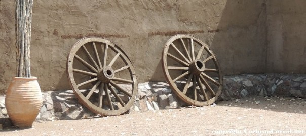 Balance - Two weathered cart wheels leaning against an adobe wall.