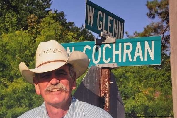 Glenn wearing a straw hat for warm weather.  A road sign behind him for the intersection of W. Glenn and N. Cochran streets.