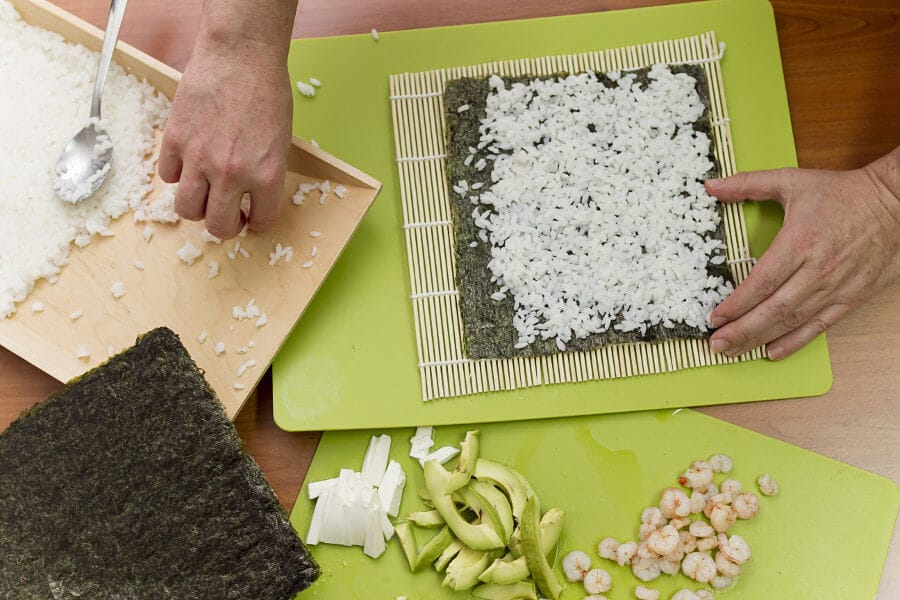 Extendiendo arroz para hacer sushi