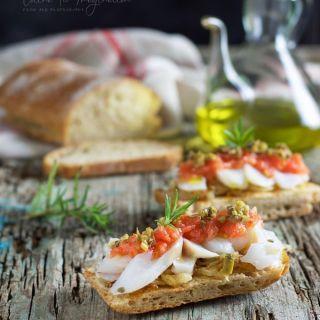Bacalao confitado en tosta con cebolla caramelizada y tomate