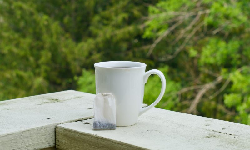 Mug Filled with Coffee Next to a Steeped Coffee Bag