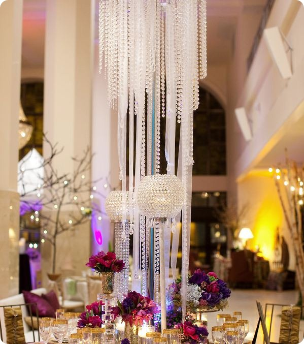 Tall hanging crystal chandelier centerpiece  and candle holder with crystal ball top mixed with jewel tone flowers and gold etched barware.  Fabulous.