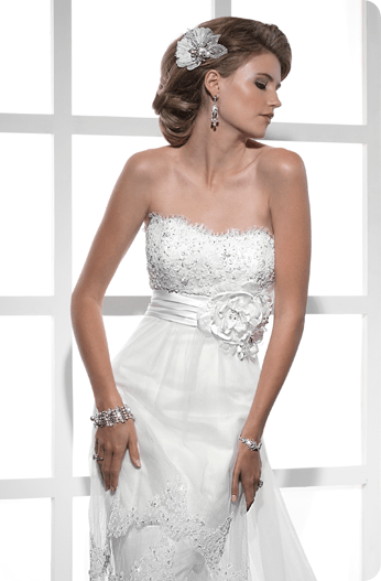 Stunning corded lace glistening with beaded embellishments softly accents this sheath tulle silhouette. Tiers of lace create a cutaway accent and beautifully cascade toward the scalloped hemline. A satin band with a gorgeous array of handmade flowers highlights the natural waist.