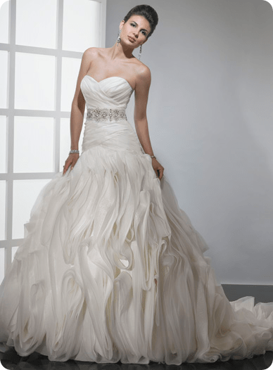 Chic Organza and Tulle create this spectacular, high-fashion look. The asymmetrical waist features a stunning jewel encrusted band accent encircling the natural waist. Vertical swirls move throughout the skirt adding drama and intrigue to this fascinating silhouette.