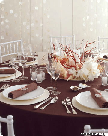 Assortment of large shells and painted manzanita branches to resemble coral surround a hurricane with a bright white candle