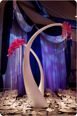 art unusual vases and statues with pink orchids and purple table linens and hanging crystals