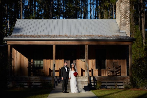 Elegantly dressed bride and groom on the porch of a rustic Savannah cabin