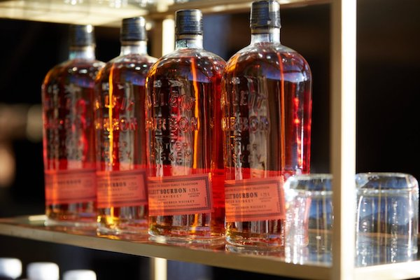 bottles of Bulliet Bourbon sitting on gold shelves in the Bourbon and Cigar Laoungs