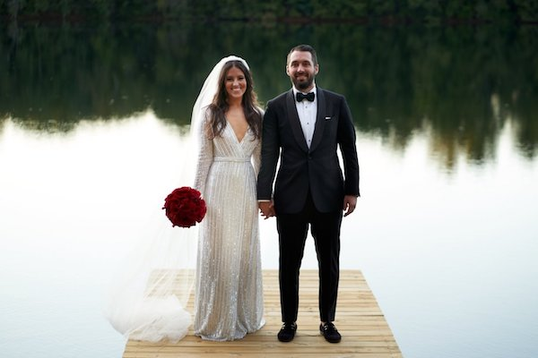bride and groom holding hands while standing on a floating dock over lake