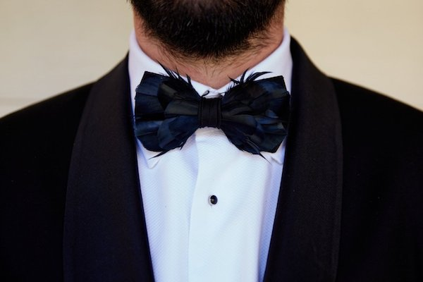 groom in a classic black tuxedo wearing a black feather bow tie
