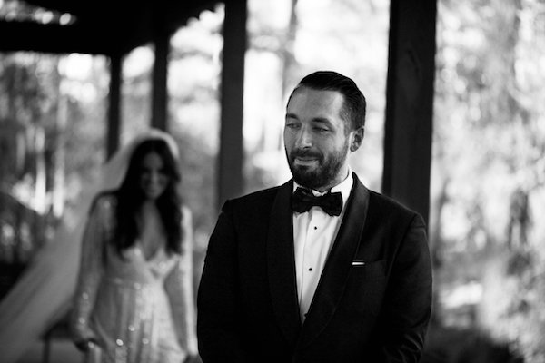 black and white photo of bride walking up behind groom for their first look