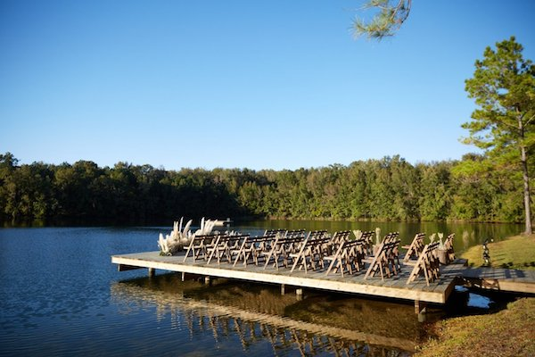 floating dock on a like set for a wedding ceremony with wooden chairs