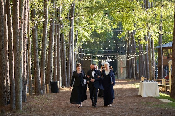 wedding party in formal black tie walking though woods