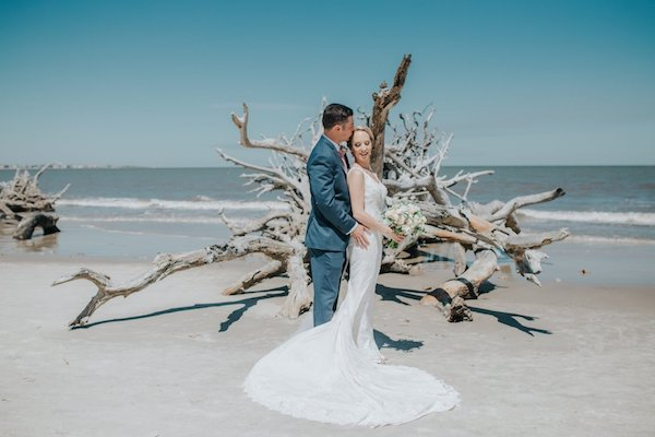 bride and groom in beach at Jekyll Island surrounded by driftwood
