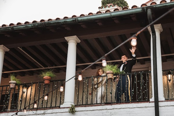 bride and groom waving from the balcony of Crane Cottage on Jekyll Island